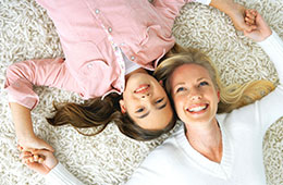 woman & daughter laying on carpet together